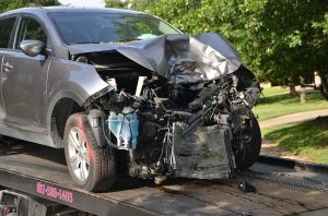 car accident personal injury lawyer smashed silver sportscar on the back of a towtruck