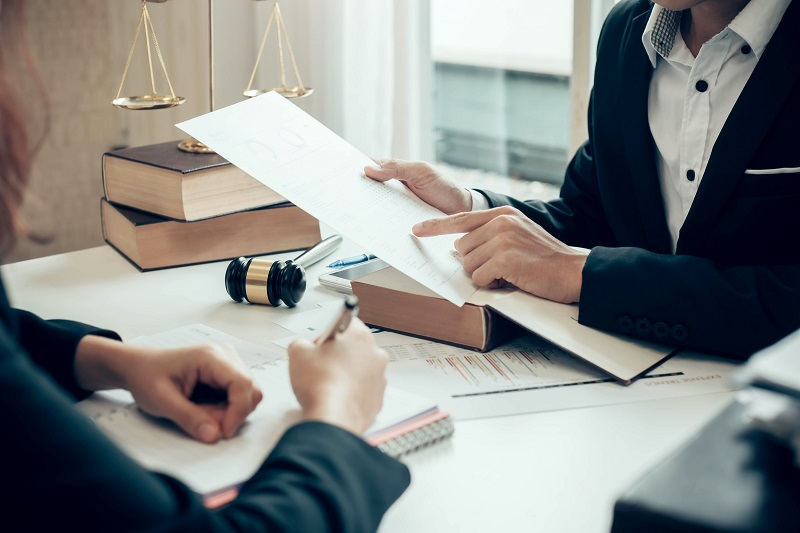 Business person and attorney at desk looking at documents together   Business Bankruptcy Attorney   Alfred Abel Law Offices