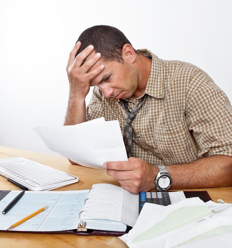 Businessman looking worried while looking through bills and checkbook | Business bankruptcy frequently asked questions | Alfred Abel Law Offices